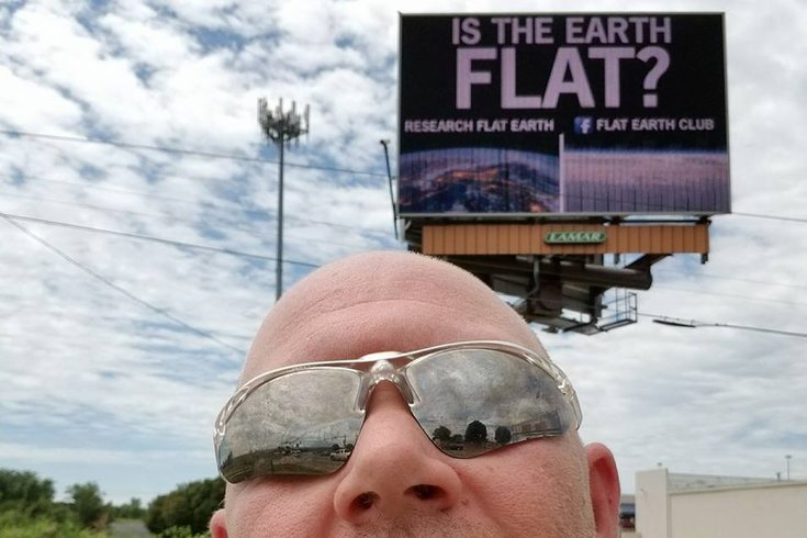 Flat Earth Billboard Image Taken By Man With Bald, Round, Dome Head